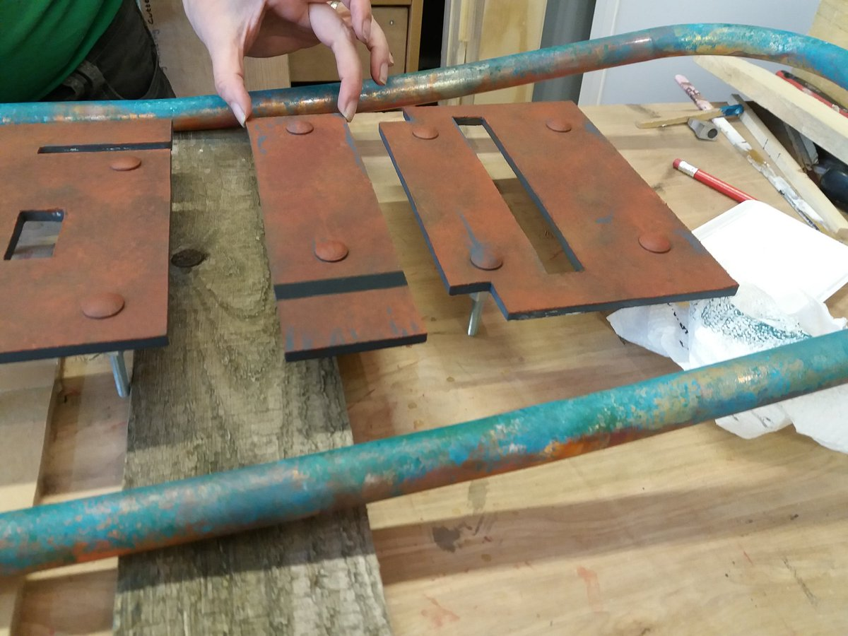close up of rust effect letters inside a verdigris effect copper pipe frame
